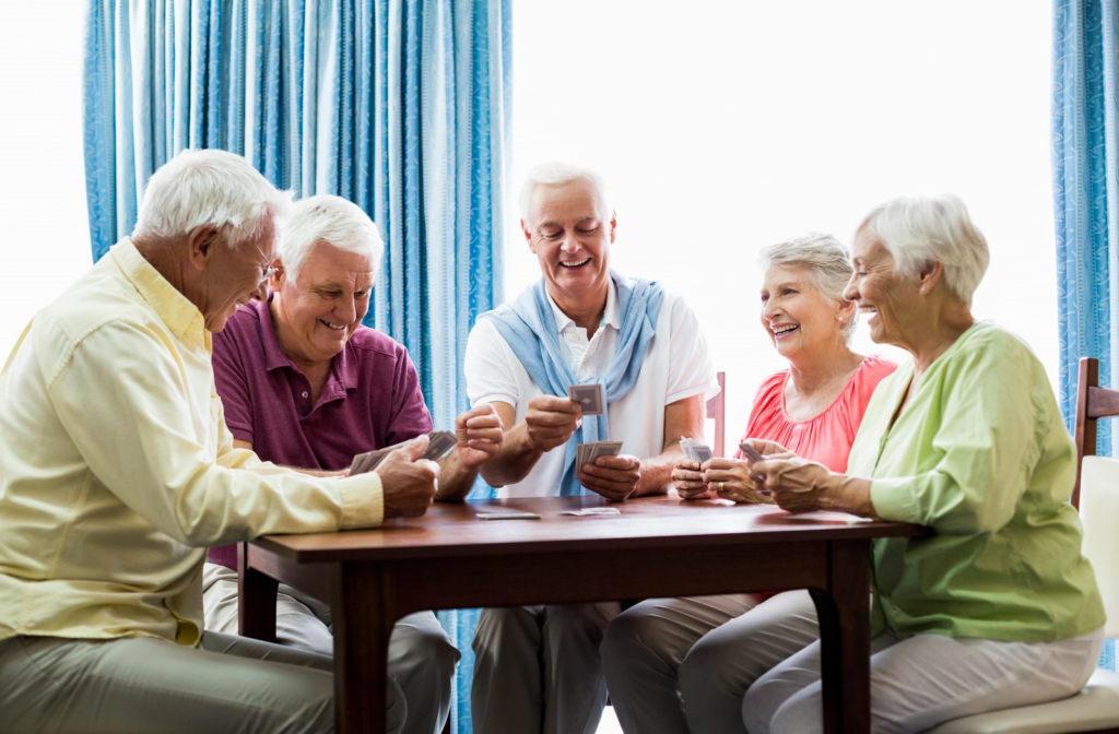 Elders playing cards together in senior home